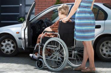 woman pushing a wheelchair next to a silver car