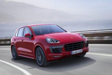 Red Porsche Cayenne driving round corner