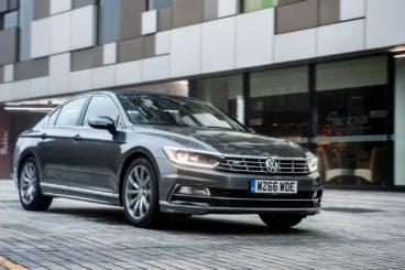 dark grey Volkswagen Passat driving in the city