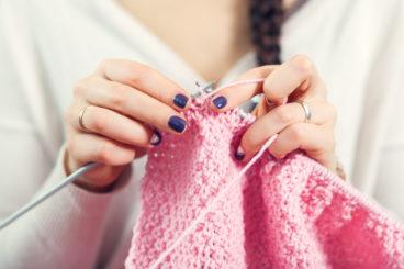 woman knitting a pink garment