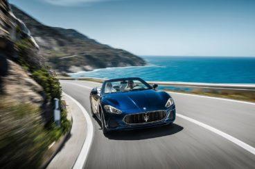 metallic blue Maserati GranCabrio Convertible driving down tropical road corner