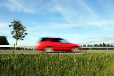 red car speeding through quite road