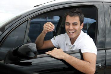Happy Hispanic man showing the key of his new car