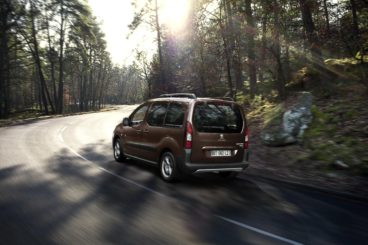 metallic peugeot partner tepee diesel estate driving on tarmac road in forest setting