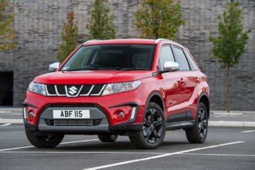 a red Suzuki vitara parked in tarmac parking lot