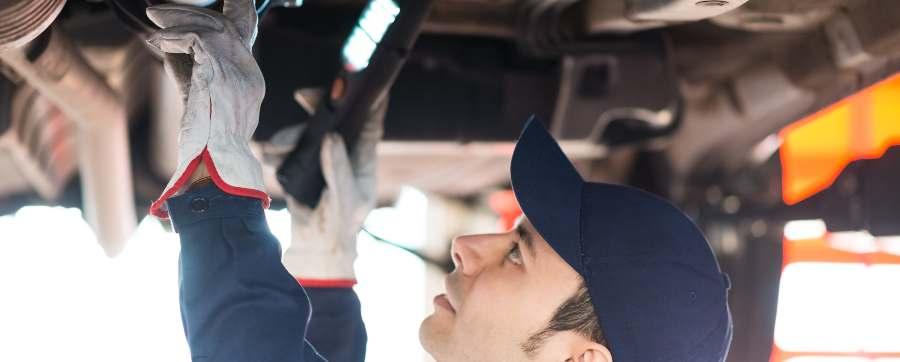 Mechanic examining underside of car